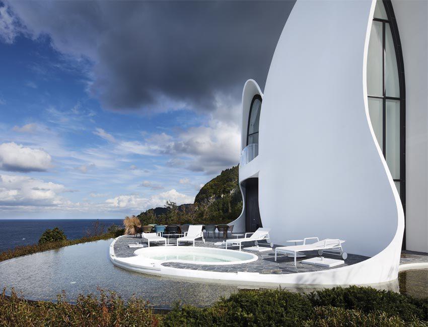 Foto van de architectuur en het buitengedeelte van het Healing Stay Kosmos designhotel, incluis indrukwekkende infinity pool.